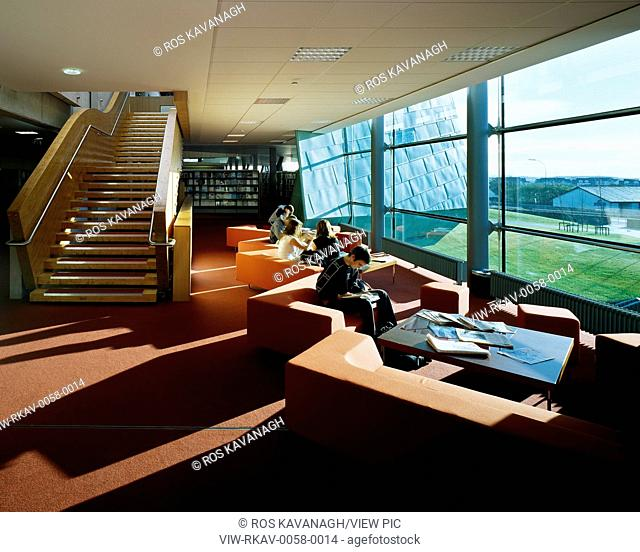 Galway-Mayo Institute of Technology, Galway, Ireland. Architect: Murray O'Laoire, 2003. View of seating area in library showing stairs, shelving, seating