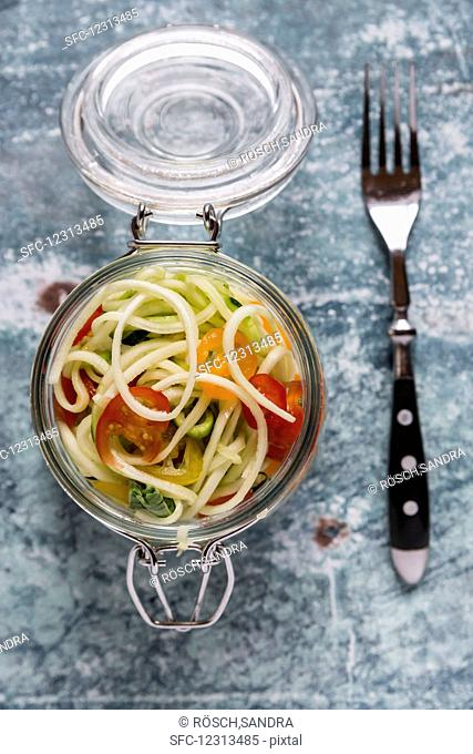 Zoodles (zucchini noodles) in a glass jar with tomatoes and basil