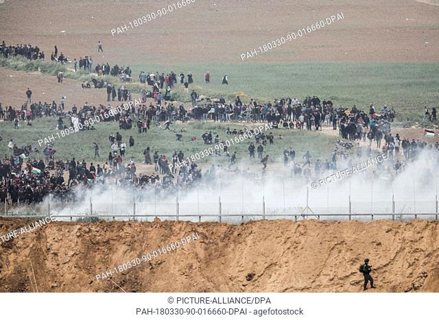 dpatop - A picture taken from the Israeli side of the Israeli Gaza border shows Palestinians marching to the border area amidst tear gas smoke fired by Israeli...