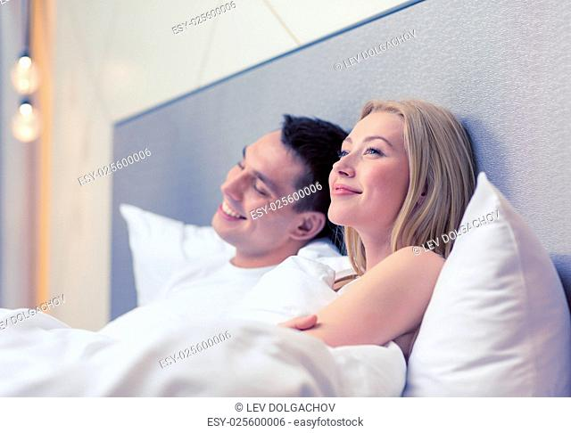hotel, travel, relationships, and happiness concept - happy couple dreaming in bed