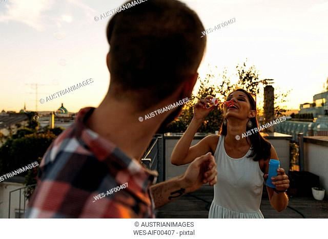 Young woman blowing soap bubbles on roof terrace while her boyfriend watching her