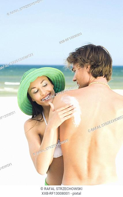 woman putting suntan lotion on beach