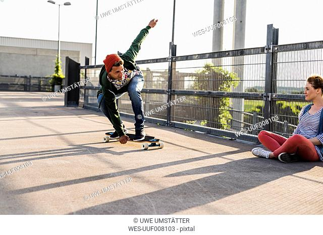 Young couple with skateboard on parking level