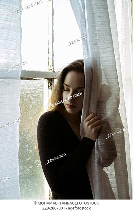 Sad young woman hands on the blinds by the window
