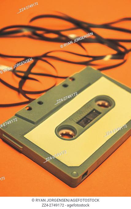 Toned retro cassette mix tape on stereotypical 1980s orange background. 80s audio objects