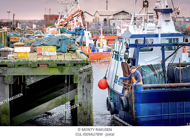 Fishermen tying up trawler in harbour at dusk