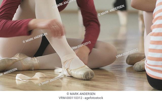 ballerina putting on pointe shoes