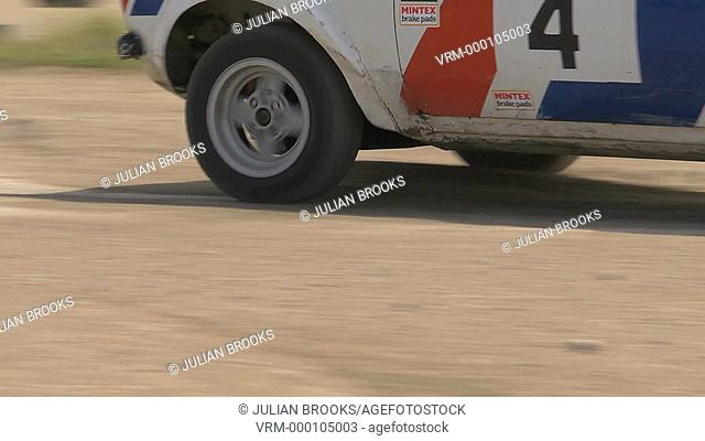 Rally car cornering - detail of wheels and track - lots of dust