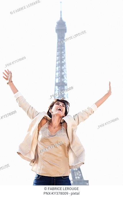 Woman shouting in excitement with the Eiffel Tower in the background, Paris, Ile-de-France, France