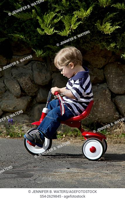 A young boy riding a red trike outdoors