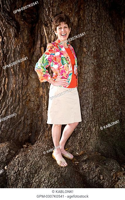 Portrait of mid adult woman standing near tree trunk