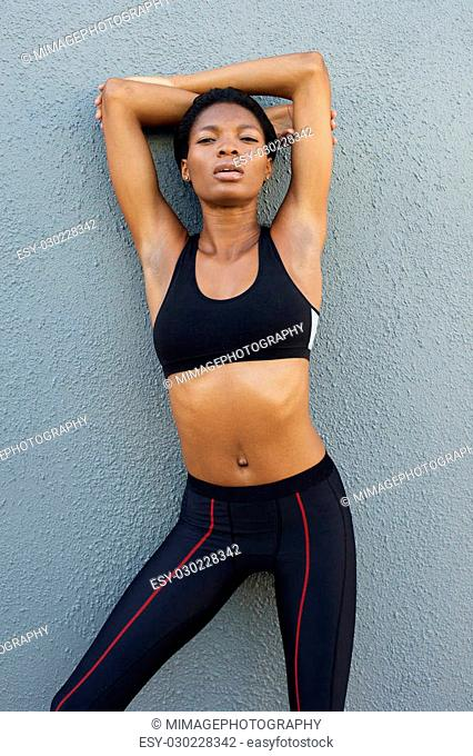 Portrait of a sporty black female woman against gray background