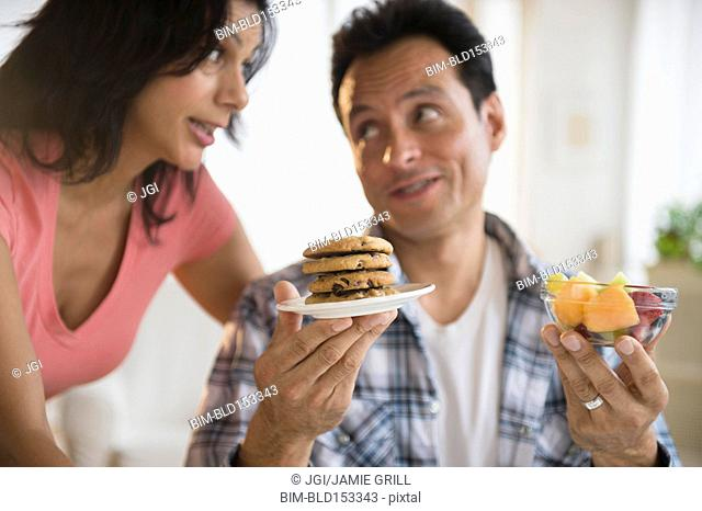 Couple choosing between healthy and unhealthy snacks