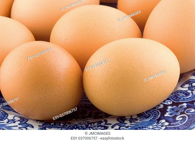 Fresh brown eggs on an antique blue and white china plate