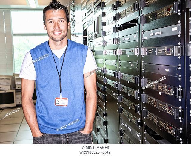 Portrait of a Caucasian male technician in a large server room