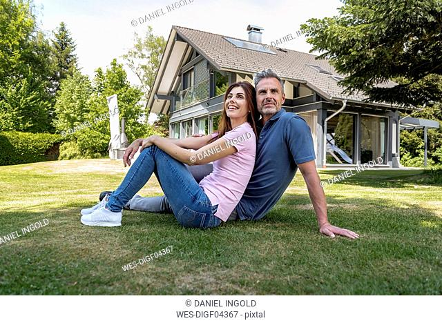 Happy couple sitting in garden of their home