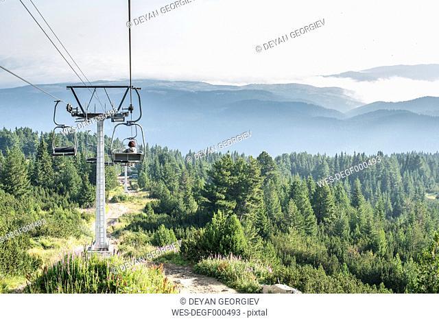 Bulgaria, Rila Mountains, senior woman using chairlift