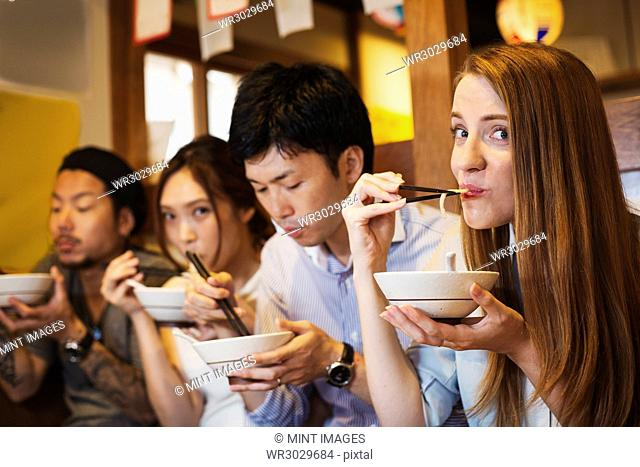 Four people sitting sidy by side at a table in a restaurant, eating from bowls using chopsticks