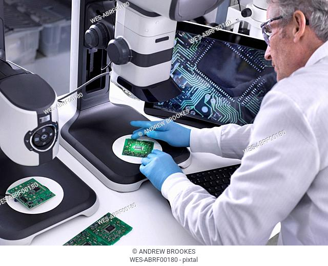 Engineer using a 3d stereo microscope for quality control in the manufacturing of circuit boards for the electronics industry