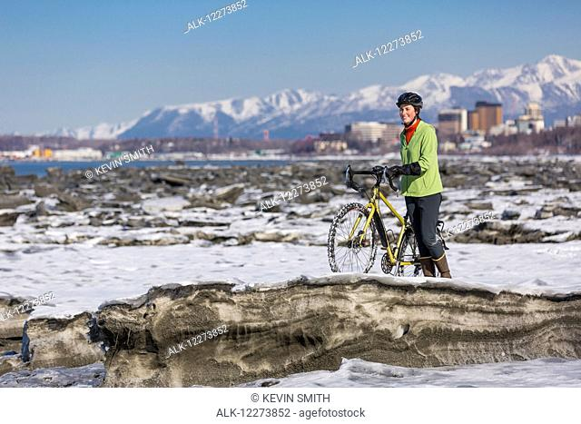 A young woman stands with her studded tire bicycle amongst the ice chunks in the Cook Inlet next to the Tony Knowles Coastal Trail, Anchorage