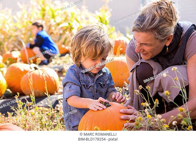 Caucasian mother and son in pumpkin patch