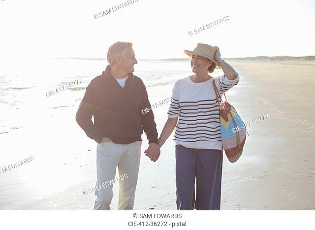 Smiling mature couple holding hands and walking on sunny beach