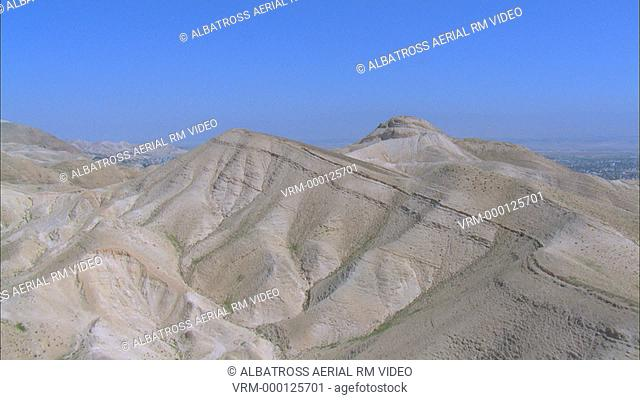Aerial view approach to the city of Jericho over summit or ridge of Judean mountains