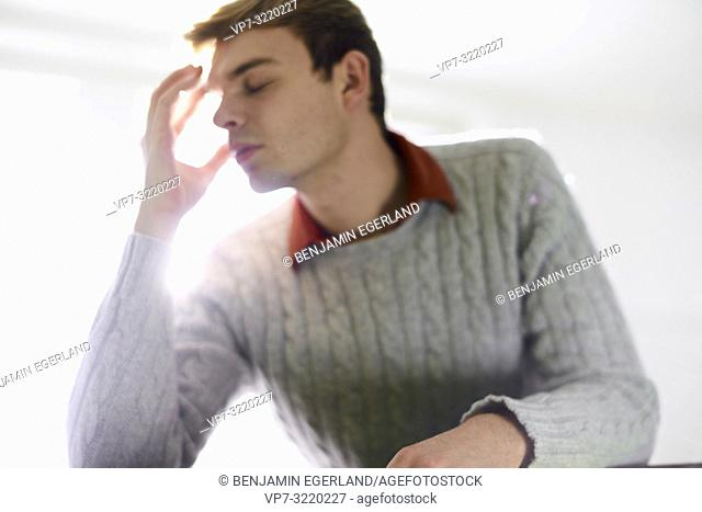Young desperate man with hand at head, burnout, student, business man, exhausted, stressful