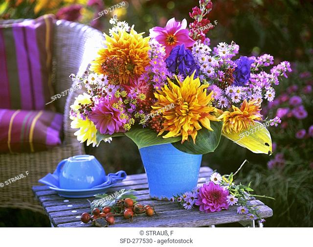 Autumnal arrangement of dahlias and asters on garden table