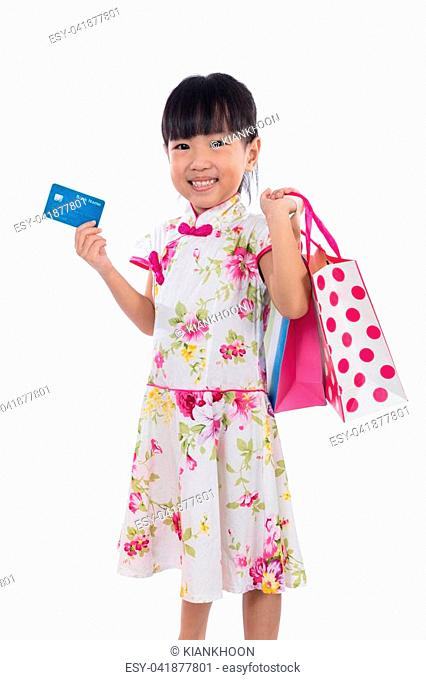 Asian Chinese little girl wearing cheongsam holding shopping bags with credit card in isolated white background