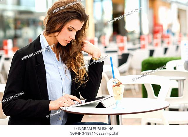 Portrait of a woman looking at her tablet computer, sitting in a coffee shop