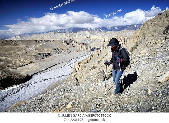 Trekker going down into a canyon between Yara and Tangge. Nepal, Gandaki, Upper Mustang (near the border with Tibet). Model Released