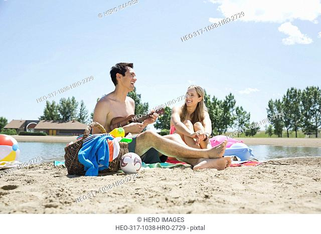 Young man playing ukulele for woman on beach