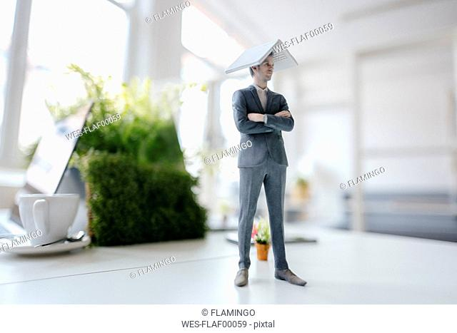 Businessman figurine standing on desk, balancing a laptop on top of his head
