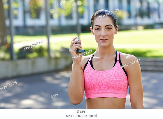 Young woman holding inhaler