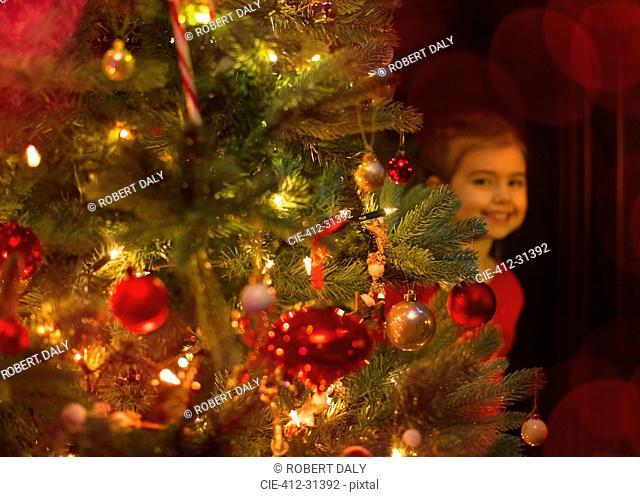 Portrait smiling girl hiding behind Christmas tree