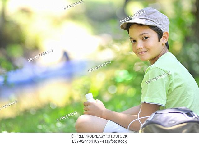 Young boy sitting in the grass and drinking a milk drink