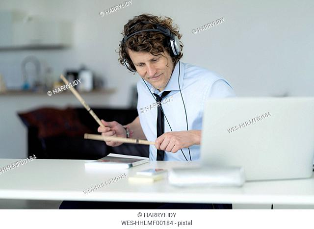 Businessman wearing headphones and drumming on his desk