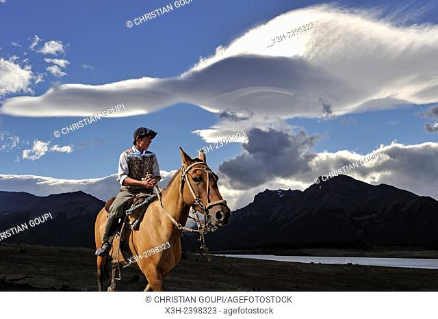 young ''gaucho'' on horseback under lenticular clouds, estancia Nibepo Aike on the Argentino lakeshore, around El Calafate, Patagonia, Argentina, South America