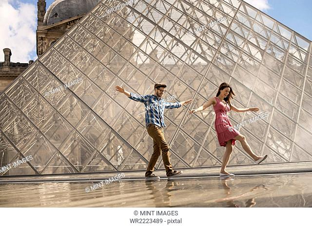 A couple in the courtyard of the Louvre museum, by the large glass pyramid. Fountains and water