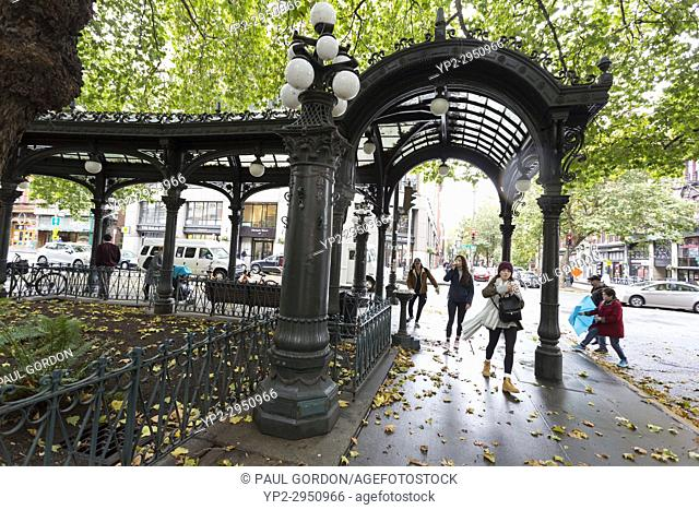 Seattle, Washington: Visitors pass through the Iron Pergola at Pioneer Square as the first storm of the season lashes Seattle with high winds and rain