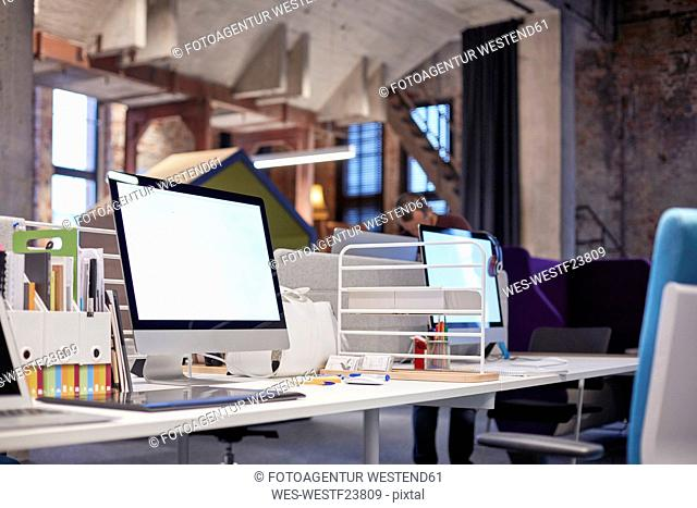 Desk in modern office with PCs
