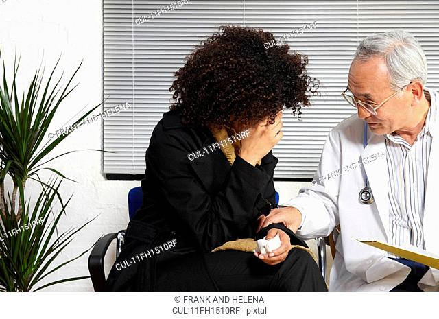 Young woman talking to doctor