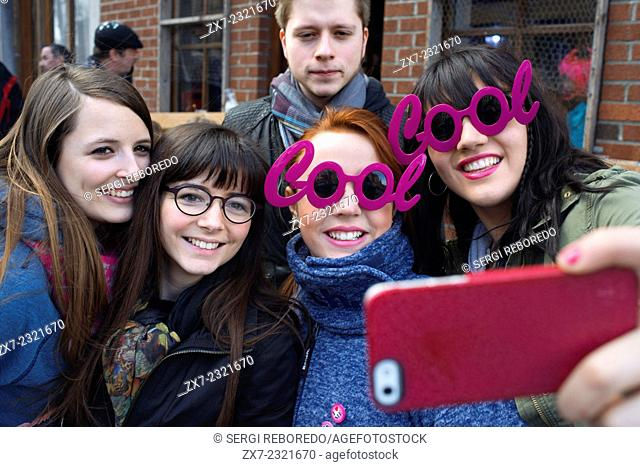 Teenagers taking selfies himself with pink fashion glasses of Cool. Music, dance, party and costumes in Binche Carnival. Ancient and representative cultural...