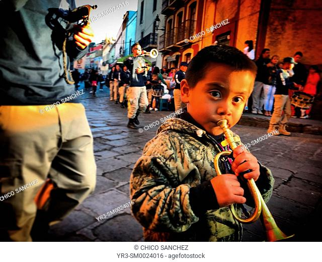 A boy plays the cornet during a parade to Our Lady of Guadalupe in Guanajuato, Mexico