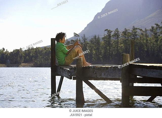 Solitary young man sitting on lake jetty, looking at mobile phone message, profile