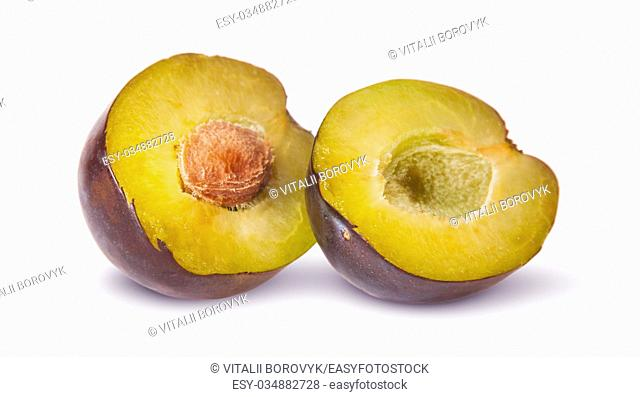 Two halves of violet plums near isolated on white background