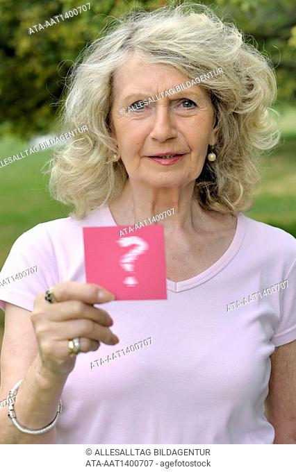 Elderly woman holding a card with a question mark