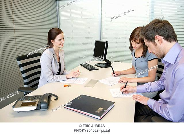 Couple signing agreement form in a real estate agent's office