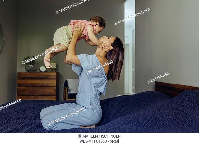 Mother lifting up her baby girl on bed